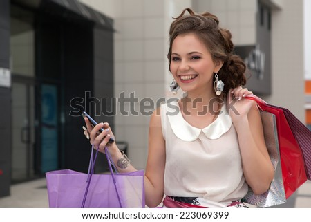 Shopping young beautiful happy girl with colored bags with phone in hand