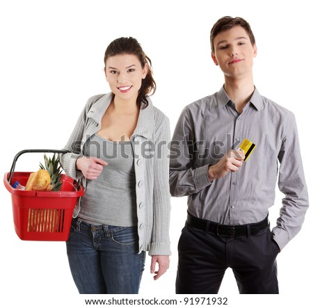 Shopping young couple with grocery items. Isolated over white background. - stock photo