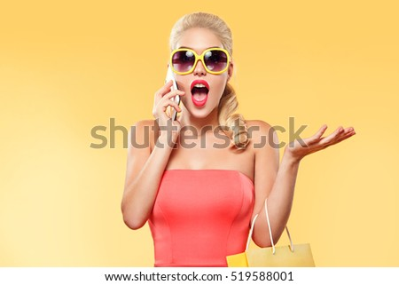 Shopping. Young smiling woman holding bag and talk by mobile phone make her thumb up in black friday holiday. Girl on yellow background with copy space