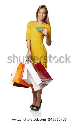 Shopping young woman in the yellow with bags and a credit card isolated on white background - stock photo
