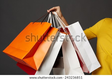 Shopping young woman in the yellow with bags on black background - stock photo