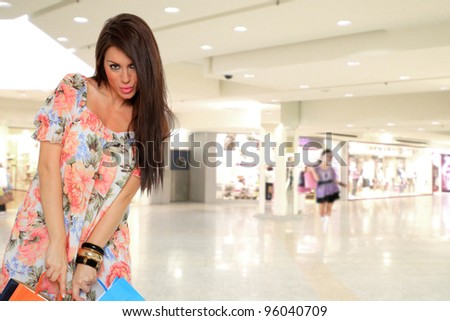 Shopping young woman smiling with bags  in the shopping mall. - stock photo