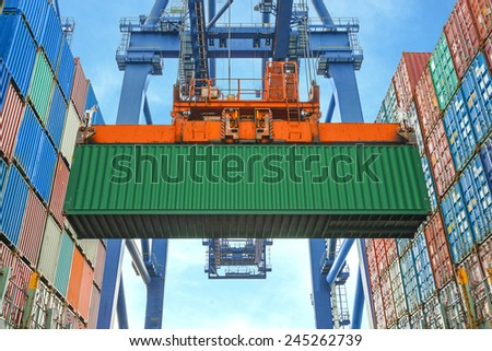 Shore crane loading containers in freight ship - stock photo