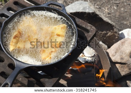 Shore lunch of frying fish in a cast iron pan on an outdoor grill - stock photo