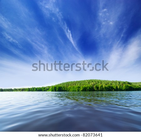 Shore of forest lake under blue sky - stock photo