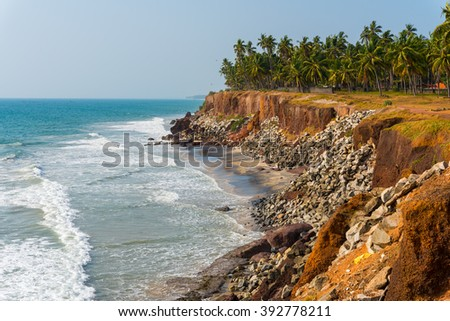 Shore protection measures in India - steep coastline strengthened by stones. Coastline of Edava village, around 2 km away to the North from resort Varkala, Kerala, India - stock photo