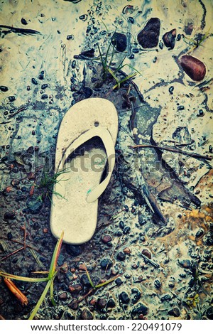 Shoreline contaminated with garbage and hazardous toxic chemical gasoline waste.  A discarded child sandal serves an iconic reminder of the human carbon footprint. Filtered for a retro, vintage look.  - stock photo