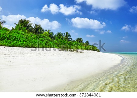 Shoreline of a tropical island in the Maldives and view of the Indian Ocean. - stock photo