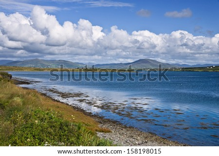 Shoreline on Valentia Island, near the Ring of Kerry, Ireland. A peaceful scene of clean blue water, fluffy clouds in a clear sky and distant mountains. - stock photo