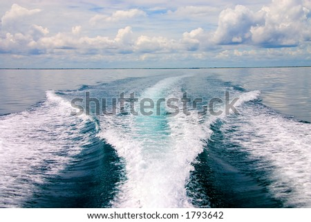 Shoreline shrinking in the distance behind boat - stock photo