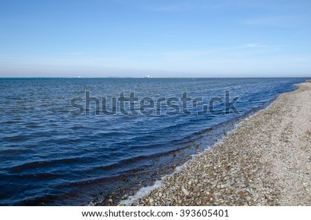 Shoreline with pebbles and blue water at the swedish island Oland in the Baltic Sea - stock photo