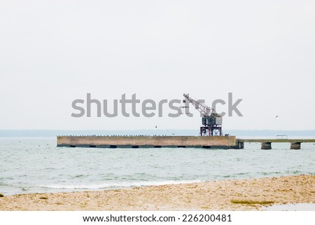 Shoreline with pier and crane during rough autumn weather - stock photo