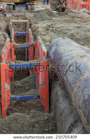 Shoring supports walls of a trench through metal framework and protect workers from cave-ins when excavating a trench for repairs or new construction. Selective focus. - stock photo