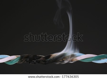 Short circuit, burnt cable, isolated on black - stock photo
