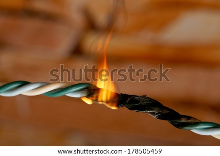 Short circuit, burnt cable, on dark color background - stock photo