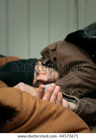 Short depth of field closeup shot of homeless man asleep on the street. Hand is in focus...rest is gradually blurred. - stock photo