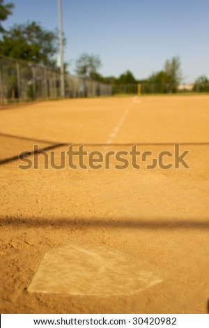 short depth of field shot of home plate looking towards third base - stock photo