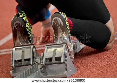 Short distance runner on gravity slope curve is in start position - stock photo