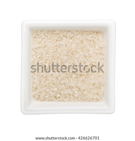 Short grain rice in a square bowl isolated on white background - stock photo