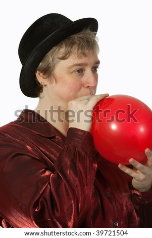 Short hair blond caucasian middle-age woman wearing a black party hat blowing up a red balloon - stock photo