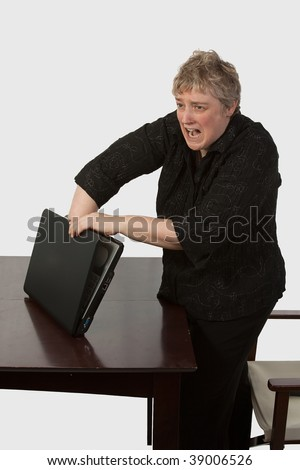 Short hair blond caucasian woman standing over brown office desk with hand stuck in laptop computer with a painful facial expression - stock photo