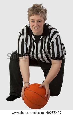 Short hair blond mother type woman wearing striped referee shirt holding a basketball over white - stock photo