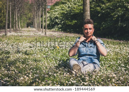 Short hair girl sitting in the grass with flowers