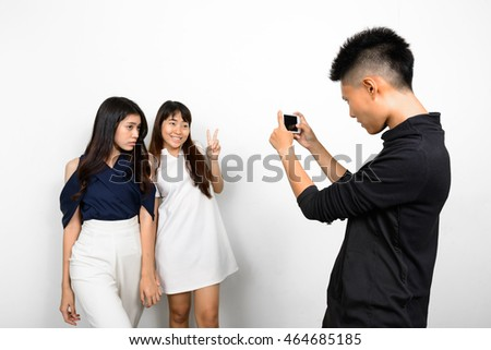 Short haired Asian woman taking picture of her friends with mobile phone