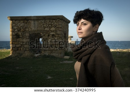 short haired brunette girl wearing a sweatshirt is standing by the seashore in front of an old building - stock photo