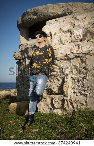 short haired brunette girl wearing a sweatshirt is standing by the seashore leaning on an old building - stock photo
