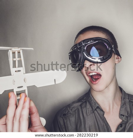 short-haired girl in retro pilot glasses with wooden plane over grey background