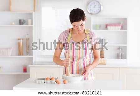 Short-haired woman preparing a cake in a kitchen - stock photo