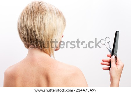 Short-haired woman with scissors and comb in his hand. - stock photo
