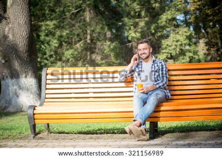 Short-haired young man holding orange cocktail and speaking over mobile phone while sitting on the bench outdoors. - stock photo