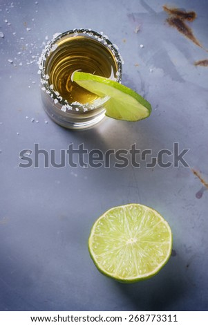 Short of tequila anejo with lime and salt over gray metal table. Overhead view. - stock photo