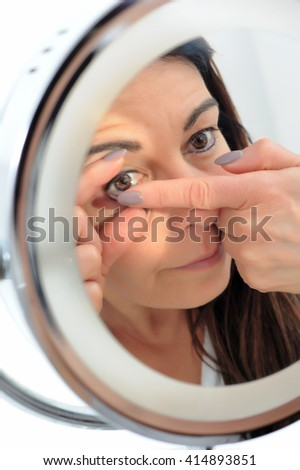 short sighted 50-year-old woman puts a contact lens in front of mirror