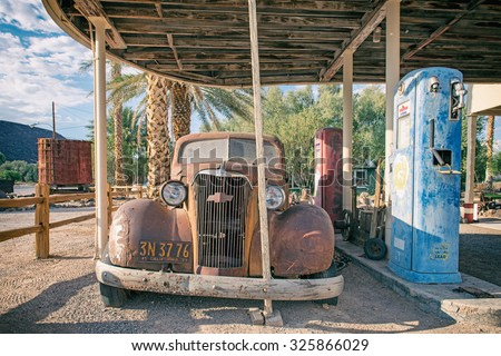 SHOSHONE, USA - SEPTEMBER 11: Abandoned gas station with its petrol pump and rusted car in Shoshone, California on 11th September 2015 - stock photo