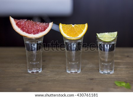 Shot drink set with diffrent citrus slices on bar background - stock photo
