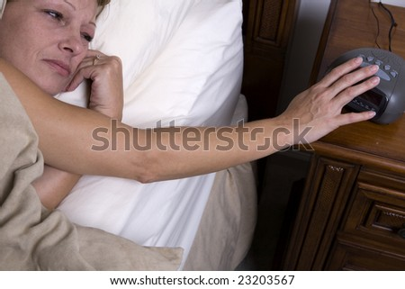 Shot from above of woman reaching for alarm clock. Sleepy, depressed look as female pushes snooze button on alarm.