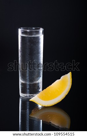 Shot glass filled with clear alcohol on a black background - stock photo