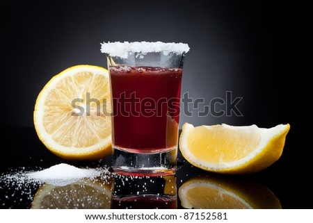 Shot glass full of dark colored alcohol  with a lemon on black background - stock photo