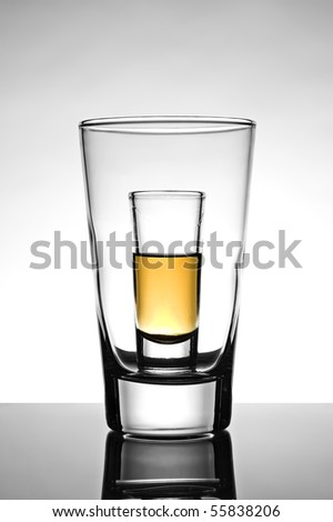 Shot glass half full with rum placed inside an empty beer glass