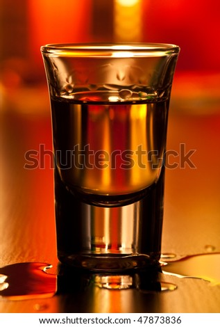 Shot glass of whiskey on a table, shallow focus