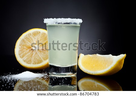 Shot glass with a lemon on black background - stock photo