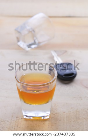 Shot glass with car keys - stock photo