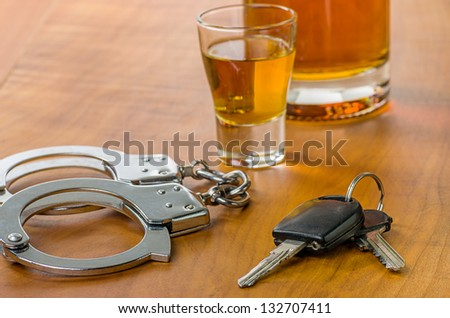 Shot glass with car keys and handcuffs - stock photo