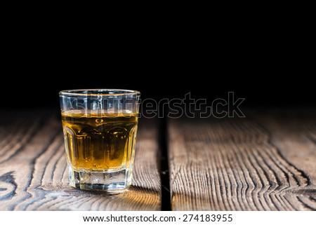 Shot glass with Whiskey (close-up shot) on wooden background - stock photo
