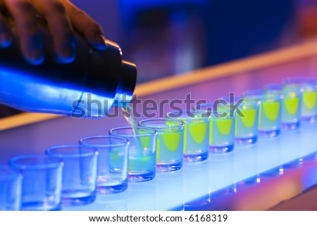 Shot glasses being poured on a bar - stock photo