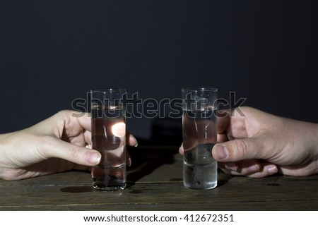 shot glasses for cocktails in the hands of male and female on the table