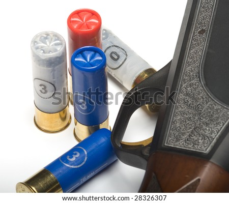 Shot-gun and the hunting cartridges on a white background. A close up - stock photo
